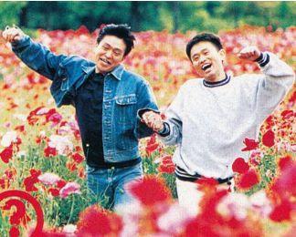 手をつないで花畑をスキップするダウンタウンのお二人